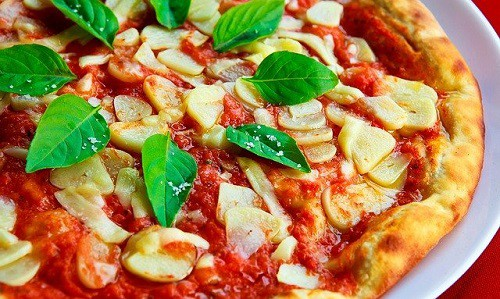 pizza topped with garlic in tomato sauce